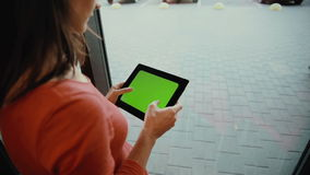 Woman using a tablet  standing by the window. green screen stock footage