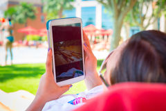 Woman using tablet on summer holidays. In Abu Dhabi Stock Images