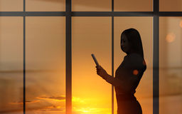 Woman using tablet at sunset Stock Images