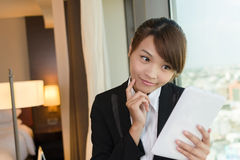 Woman using tablet and thinking. Asian business woman using tablet and thinking, closeup portrait in hotel room Stock Images