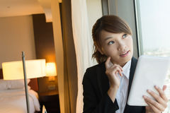 Woman using tablet and thinking. Asian business woman using tablet and thinking, closeup portrait in hotel room Stock Photos