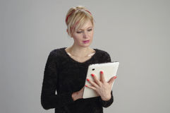 Woman using tablet. Wife temps free time available electronics technique communication laptop small worldwide worldwide communication leisure monitors woman Stock Photography
