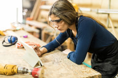 Woman using tablet in a woodshop stock images