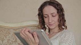 Woman using tablet. Young woman using electronic tablet sitting in sofa stock video footage