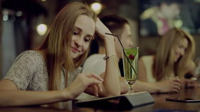 Woman using a tablet. Young smiling woman using a tablet sitting in a bar with a couple on background stock video footage