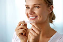 Woman Using Teeth Whitening Strip For Beautiful White Smile. White Smile. Beautiful Smiling Woman With Healthy White Teeth Applying Teeth Whitening Strip stock images