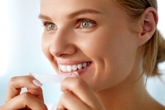 Woman Using Teeth Whitening Strip For Beautiful White Smile Stock Images