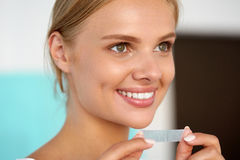Woman Using Teeth Whitening Strip For Beautiful White Smile Royalty Free Stock Photography