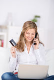 Woman Using Telephone While Doing Online Shopping Royalty Free Stock Images