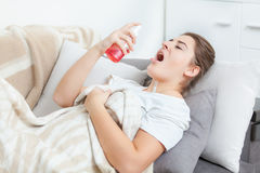 Woman using throat spray while lying on couch Royalty Free Stock Image