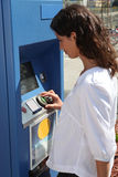 Woman using ticket machine Stock Images