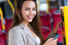 Woman using ticket machine on bus Royalty Free Stock Image
