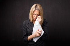 Woman using tissue to wipe her tears Stock Image