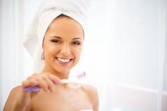 Woman using toothbrush Royalty Free Stock Image