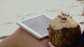 Woman using touch pad and having coconut drink. Close-up shot of a woman on the beach typing on tablet computer and drinking from coconut. Summer vacation in stock footage