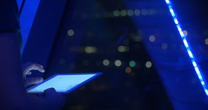 Woman using touch pad by the window at night