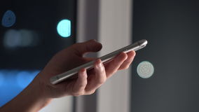 Woman using touch screen on smartphone with bokeh in city night background.  stock video footage