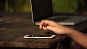 Woman using touch screen on smartphone with wooden desk.  stock footage