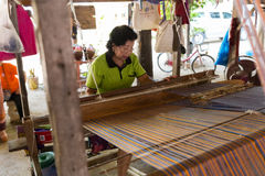 Woman using traditional loom to weave thailand textile Stock Photo