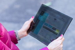 Woman using a transparent digital tablet. Hands of a woman using a transparent digital tablet on a city to retrieve informations or working royalty free stock photography