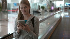 Woman using travolator in airport terminal. Waiting for flight. Using her smartphone, browsing stock video footage