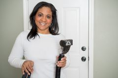 Woman With Vaccum. Woman using the vaccum on her house Stock Image