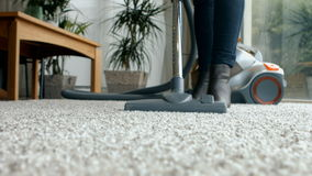 Woman using the vacuum cleaner stock footage