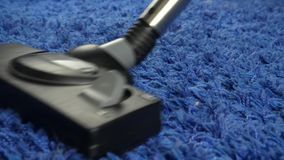 Woman Using Vacuum Cleaner Cleaning Blue Carpet