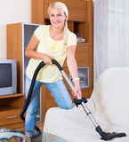 Woman using vacuum cleaner Stock Photos