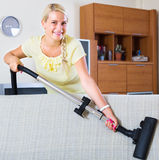 Woman using vacuum cleaner Royalty Free Stock Photography