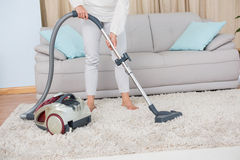 Woman using vacuum cleaner on rug Royalty Free Stock Photography