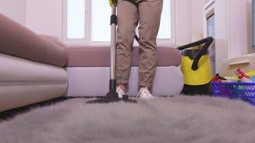 Woman using vacuum cleaner on rug. In room stock video footage