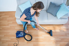 Woman using vacuum cleaner on wooden floor Royalty Free Stock Images