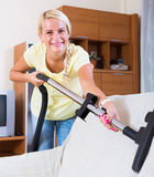 Woman using vacuum cleaner Royalty Free Stock Photos