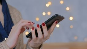 Woman using vertical black smartphone at home. Woman using vertical black slim smartphone at home. Warm bokeh light background. Entertainment and technology stock video