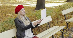 Woman using video chat app on laptop. Attractive young woman in leather jacket and red beret sitting on bench in autumn park using video chat app on laptop stock video