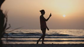 Woman using video chat while walking on the beach at sunset stock video footage