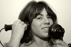 Woman Using a Vintage Phone. Young Woman Using a Vintage Telephone Royalty Free Stock Photo