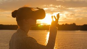 Woman using virtual reality glasses on deck of cruise ship at sunset. Woman using virtual reality headset on deck of cruise ship at sunset. Sunset light, golden Royalty Free Stock Image
