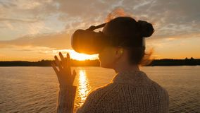 Woman using virtual reality glasses on deck of cruise ship at sunset. Woman using virtual reality headset on deck of cruise ship at sunset. Sunset light, golden Stock Images