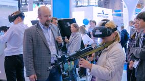 Woman using virtual reality headset and playing in shooter game. MOSCOW, RUSSIA - SEPTEMBER 8, 2017: City of Education Exhibition. Woman using virtual reality Stock Image