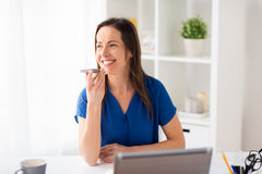 Woman using voice recorder on smartphone at office. Technology, communication and people concept - happy woman using voice command recorder on smartphone at Royalty Free Stock Images