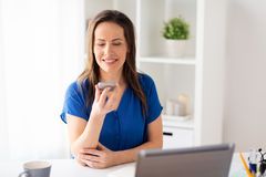 Woman using voice recorder on smartphone at office. Technology, communication and people concept - happy woman using voice command recorder on smartphone at Stock Photography