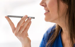 Woman using voice recorder on smartphone. Technology, communication and people concept - close up of happy woman using voice command recorder on smartphone royalty free stock images