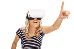 Woman using a VR goggles. And reaching to touch something with her finger isolated on white background Royalty Free Stock Image