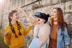 Woman using VR headset glasses 360 experience outdoor. Visual reality concept. Excited three girls experiencing virtual reality. royalty free stock images