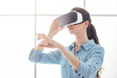Woman using a VR headset. Young woman experiencing virtual reality, she is wearing a VR headset and interacting with a virtual environment, innovative technology Stock Photos