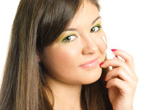 Woman using a wadded stick. Beautiful young brunette woman removing makeup with a wadded stick Royalty Free Stock Image