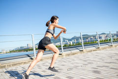 Woman using waerable smart watch and running Stock Photos