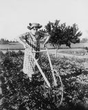 Woman using walking plow in garden Royalty Free Stock Image